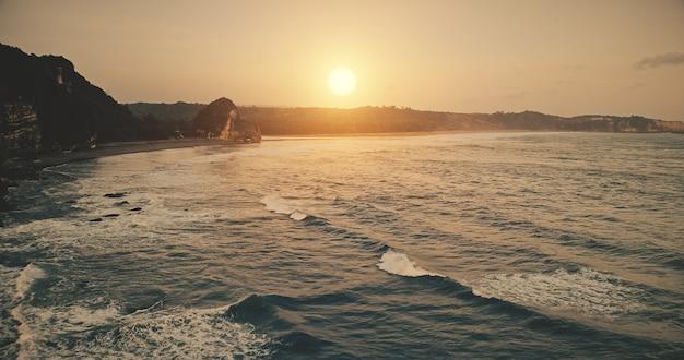 Skały zachód słońca brzegu oceanu falami na powierzchni wody w widoku z lotu ptaka