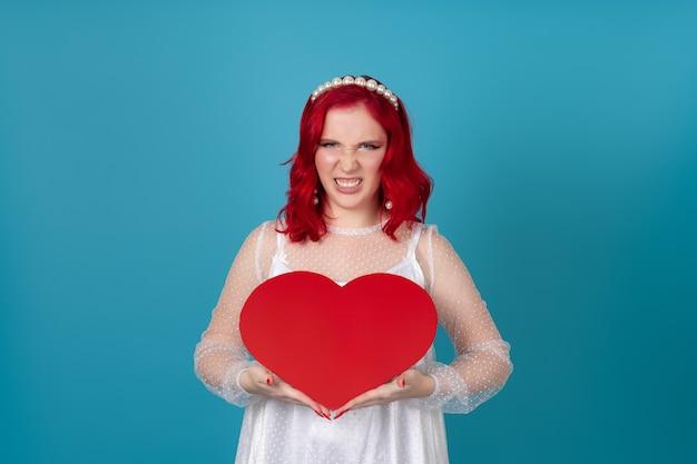 Skandaliczna, wściekła, sfrustrowana, drapieżna młoda kobieta trzyma odsłaniające zęby duże czerwone papierowe serce