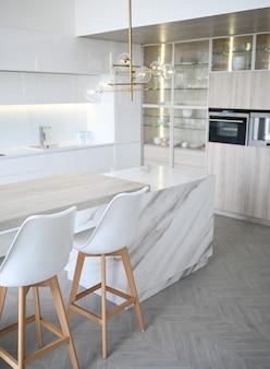 Skandynawska pusta klasyczna nowoczesna luksusowa kuchnia z drewnianym, białym, marmurowym stołem, nowymi stylowymi meblami, minimalistycznym norweskim wystrojem wnętrz. stołki barowe, szklany stojak, naczynia i szklane naczynia