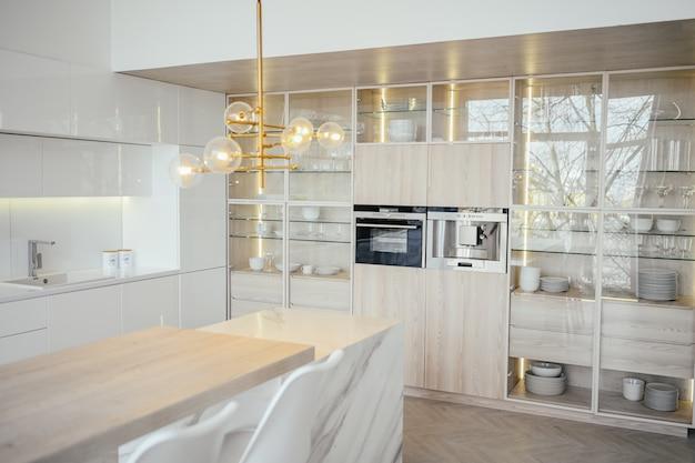Skandynawska pusta klasyczna nowoczesna luksusowa kuchnia z drewnianymi, białymi, marmurowymi detalami, nowe stylowe meble, minimalistyczny nordycki wystrój wnętrz. stołki barowe, szklany stojak, naczynia i szklane naczynia