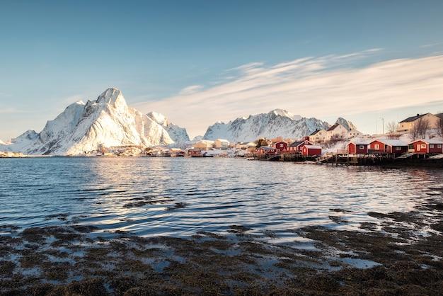 Skandynawska wioska rybacka z zaśnieżoną górą na wybrzeżu. reine, lofoty, norwegia
