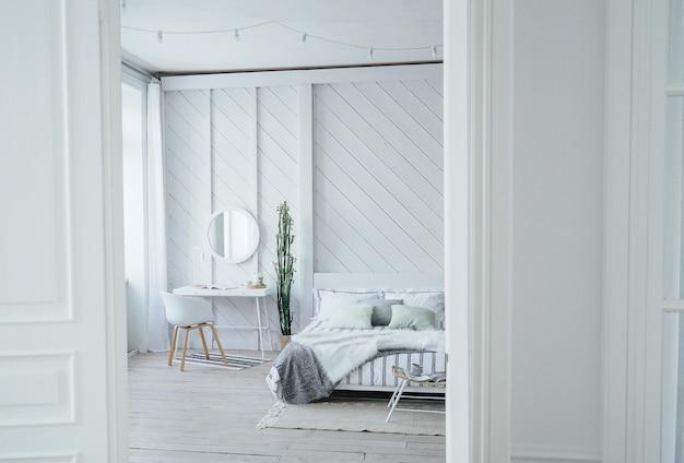 Skandynawski nowoczesny przytulny ekologiczne wnętrze, biały stół i lustro w sypialni, minimalizm