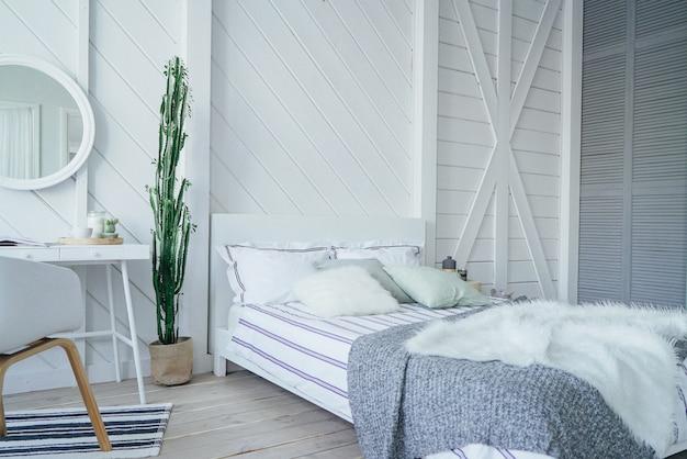 Skandynawski nowoczesny przytulny ekologiczne wnętrze, biały stół i lustro w sypialni