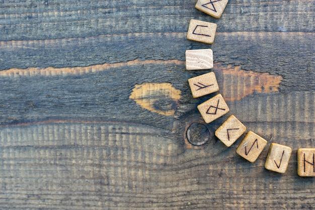 Skandynawskie drewniane runy na starym drewnianym stole. starszy futhark.