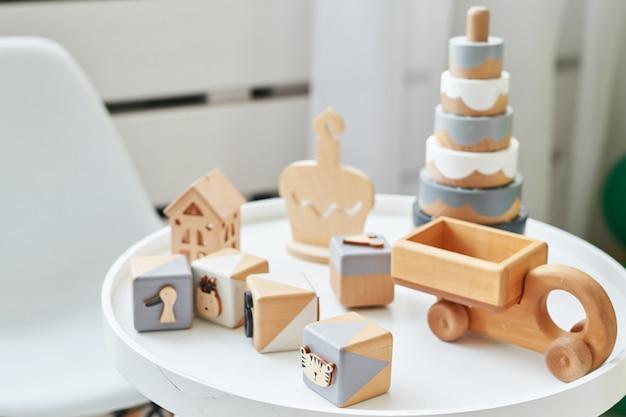 Skandynawskie meble dziecięce. skandynawski stół dziecięcy i drewniane zabawki edukacyjne. wnętrze pokoju dziecięcego w stylu loftu. drewniane zabawki, kostki, piramida i samochód.