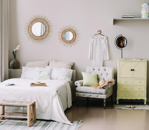 Skandynawskie nowoczesne wnętrze sypialni z szerokim łóżkiem z fotelem poduszkami i dekoracjami