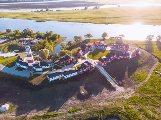 Skandynawskie tradycyjne czerwone drewniane domy na brzegu jeziora w lecie. krajobraz wsi w finlandii. czerwone domy o zachodzie słońca w wiosce rybackiej