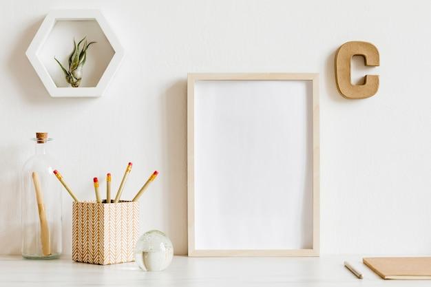 Skandynawskie wnętrze biura domowego z drewnianą ramą plakatową, akcesoriami do biura projektowego, taśmami, materiałami eksploatacyjnymi, notatkami, patyczkami memo, roślinami powietrznymi. minimalistyczna koncepcja. szablon.