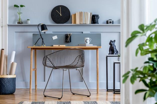 Skandynawskie wnętrze biura domowego z drewnianym biurkiem, designerskim krzesłem, boazerią z półką, rośliną, lampą stołową, artykułami biurowymi i eleganckimi akcesoriami w nowoczesnym wystroju domu.