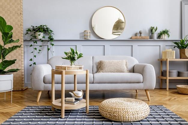 Skandynawskie wnętrze salonu z designerską szarą sofą, drewnianym stolikiem kawowym, tropikalnymi roślinami, półką, lustrem, meblami, poduszką w kratę, czajnikiem, książką i eleganckimi akcesoriami osobistymi w wystroju domu.