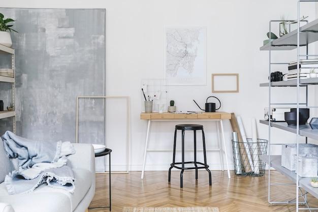 Skandynawskie wnętrze z drewnianym biurkiem, krzesłem, designerską sofą, stolikiem kawowym, regałem i akcesoriami artystycznymi