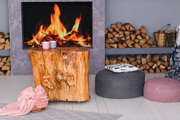 Skandynawskie wnętrze z kominkiem, stołem kikutowym, stertą kłód do ognia