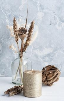 Skandynawskie wnętrze ze złocistymi suchymi kwiatami i zapaloną świecą