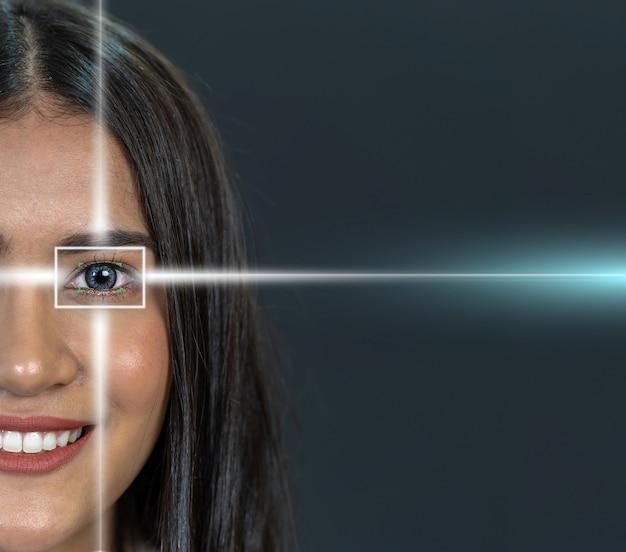Skanowanie oczu azjatyckiej młodej kobiety za pomocą światła laserowego na ciemnym tle