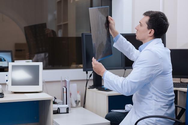 Skanowanie rentgenowskie. miły, przystojny, przyjemny radiolog siedzi na krześle i patrzy na obraz tomografii komputerowej podczas pracy w laboratorium ct