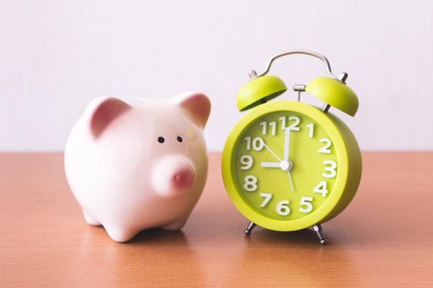 Skarbonka, budzik i monety. dla rozwijającego się biznesu. czas na oszczędzanie koncepcji.
