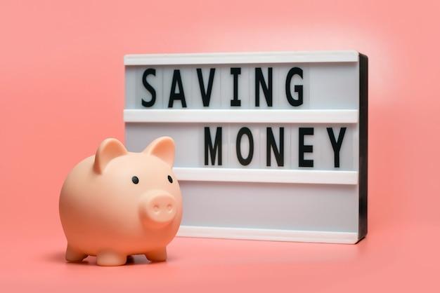 """Skarbonka i lightbox z napisem """"oszczędność pieniędzy"""" na różowej powierzchni."""