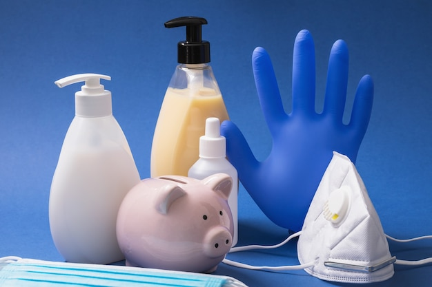 Skarbonka i różne środki ochrony indywidualnej na stole koncepcja wydatków na produkty higieniczne podczas pandemii koronawirusa