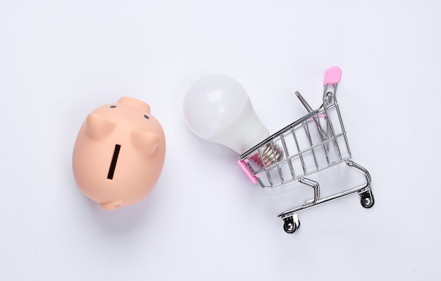 Skarbonka i wózek supermarketu z żarówką led na białym tle. oszczędzanie energii
