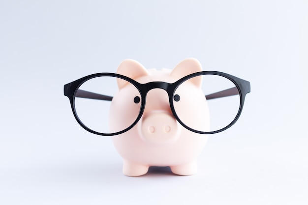 Skarbonka nosić okulary na szary stół zbliżenie. oszczędność pieniędzy lub koncepcja oszczędności