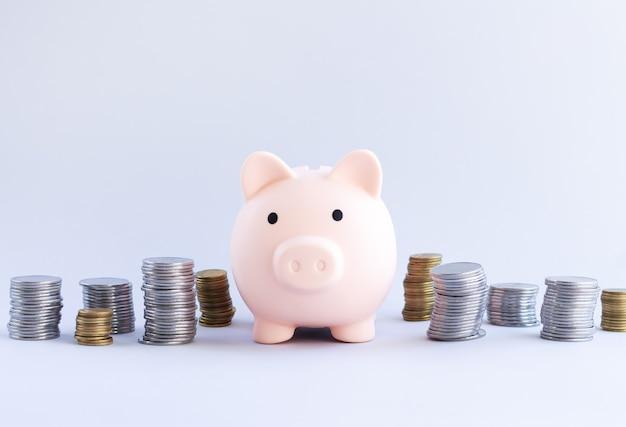 Skarbonka obok stosów monet, koncepcji oszczędzania i inwestycji