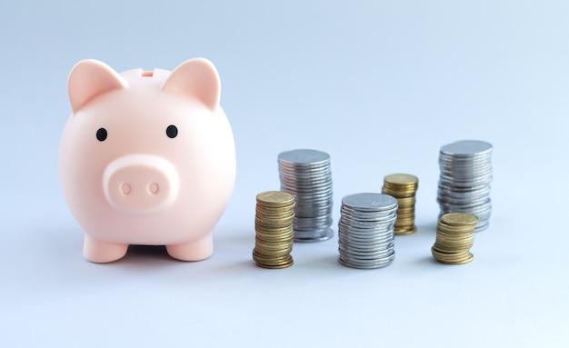 Skarbonka obok stosów monet na szarym tle. koncepcja oszczędnościowo-inwestycyjna