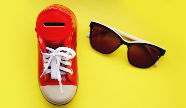 Skarbonka w formie trampek. okulary przeciwsłoneczne na żółtym tle. pojęcie oszczędności na wakacjach i wakacjach. oszczędzaj pieniądze