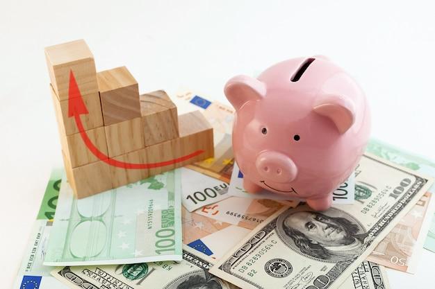 Skarbonka w kształcie świni, rosnące kostki drewna wykresowego, banknoty euro i dolary amerykańskie na na białym tle