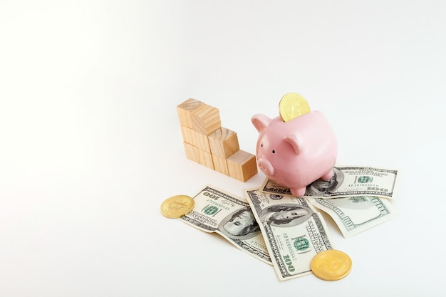 Skarbonka w kształcie świni z monetami bitcoin, klepsydrą, rosnącymi kostkami drewna wykresowego i dolarami amerykańskimi na białym tle