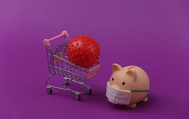 Skarbonka w masce medycznej z wózkiem na zakupy, model szczepu wirusa na fioletowym tle. zakupy w czasie covid-19, kryzys gospodarczy, gospodarka