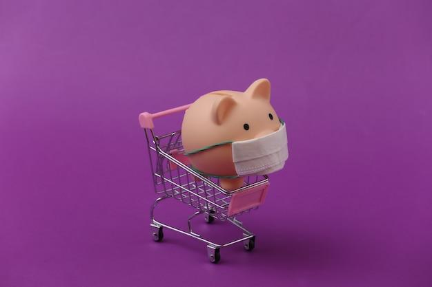 Skarbonka w masce medycznej z wózkiem na zakupy na fioletowym tle. zakupy w czasie covid-19, kryzys gospodarczy, gospodarka
