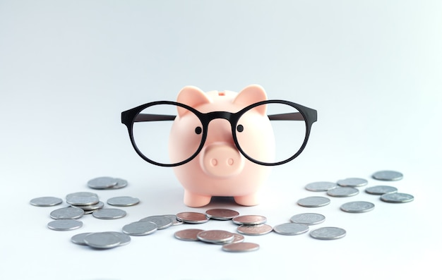 Skarbonka w okularach na biurowym stole ze stertą monet. oszczędność pieniędzy lub koncepcja oszczędności