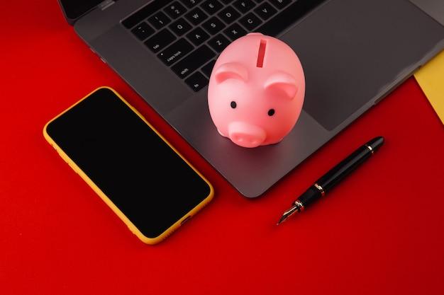 Skarbonka w pobliżu laptopa i smartfona, miejsce na tekst. koncepcja finansów i budżetu. skarbonka w kolorze różowym z gadżetami i papeterią na kolorowym tle.