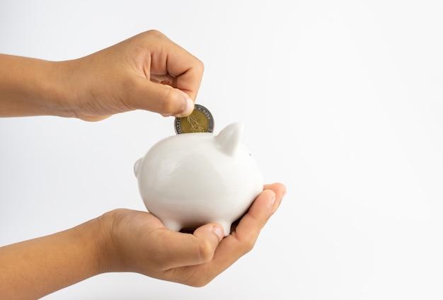 Skarbonka w ręku i wkłada monety do skarbonki z miejscem na kopię na białej ścianie.