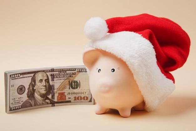 Skarbonka z boże narodzenie kapelusz kilka banknotów dolarów gotówki pieniądze na białym tle na beżowym tle. inwestycja akumulacji pieniędzy, usługi bankowe, koncepcja bogactwa. skopiuj makiety reklamowe.