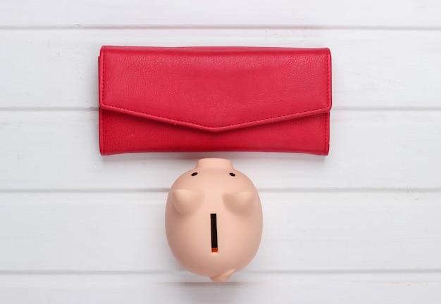 Skarbonka z czerwonym skórzanym portfelem na białej drewnianej powierzchni. widok z góry
