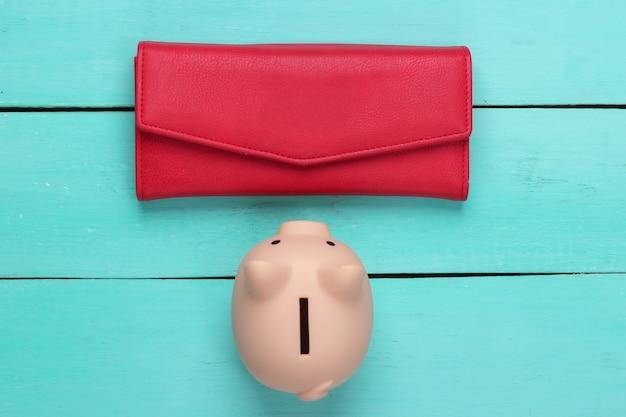 Skarbonka z czerwonym skórzanym portfelem na niebieskiej powierzchni drewnianej. widok z góry
