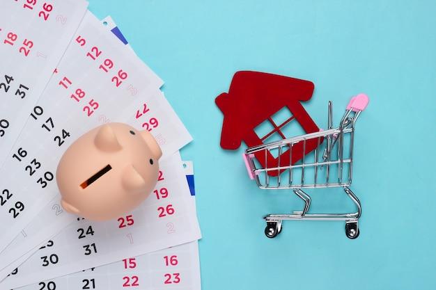 Skarbonka z kalendarzem miesięcznym, wózek na zakupy z figurką domu na niebiesko. spłata wynajmu mieszkania lub pożyczki