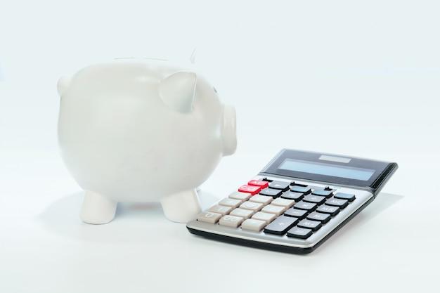 Skarbonka z kalkulatorem na białym tle
