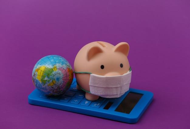 Skarbonka z maską medyczną i kalkulatorem, kula ziemska na fioletowym tle. choroba ekonomiczna. kryzys finansowy. covid-19 pandemia
