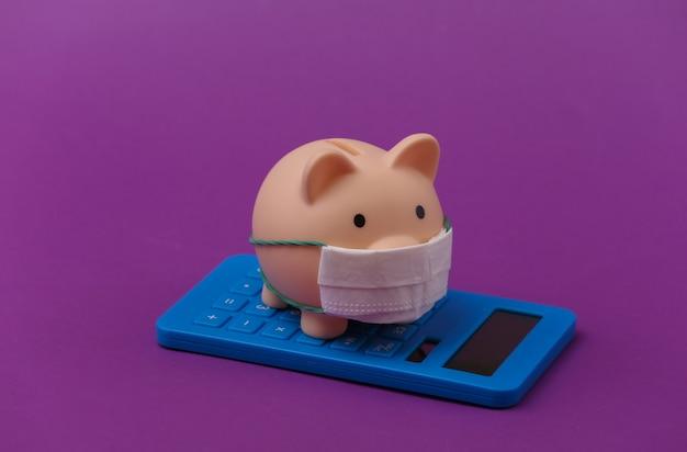 Skarbonka z maską medyczną i kalkulatorem na fioletowym tle. choroba ekonomiczna. kryzys finansowy. covid-19 pandemia