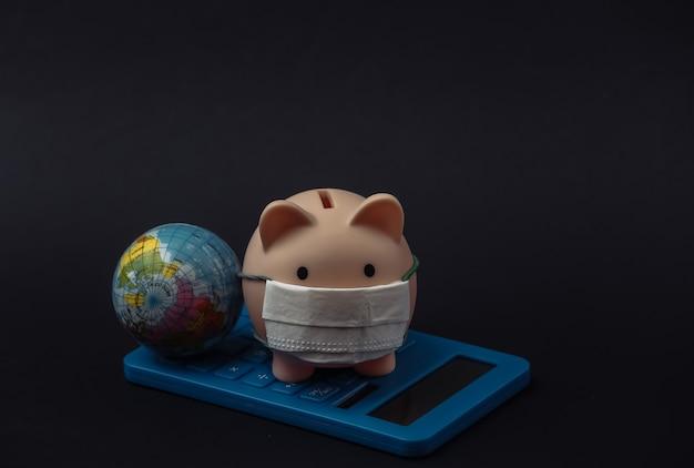 Skarbonka z maską medyczną, kulą ziemską i kalkulatorem na czarnym tle. choroba ekonomiczna. kryzys finansowy. covid-19 pandemia
