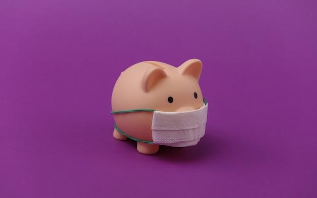 Skarbonka z maską medyczną na fioletowym tle. choroba ekonomiczna. kryzys finansowy. covid-19 pandemia