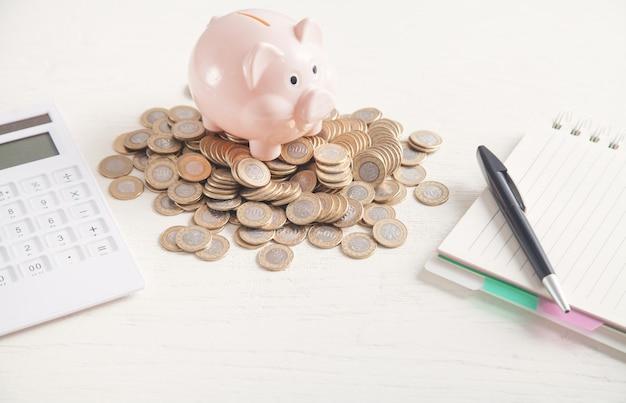 Skarbonka z monetami, kalkulatorem, notatnikiem i długopisem na biurku. oszczędzać pieniądze