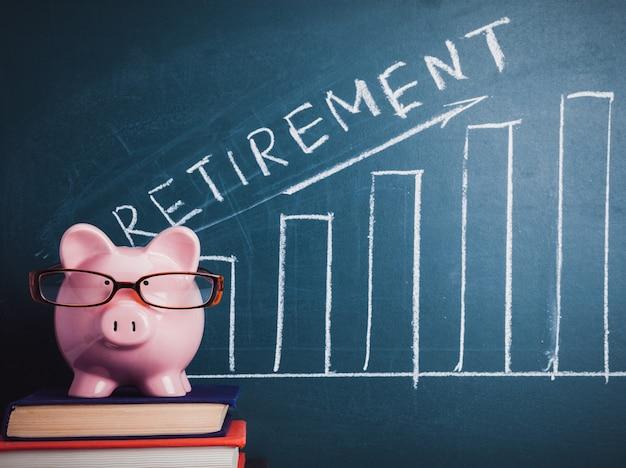 Skarbonka z okularami i planem emerytalnym na tablicy