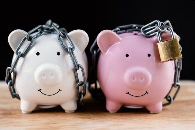 Skarbonka zablokowana, przykuta czarnym tłem, chroń oszczędności, chroń kapitał, chroń koncepcję funduszu emerytalnego.