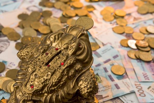 Skarbonka ze złotymi monetami leżą na ukraińskich banknotach. 500 i 1000 hrywien. nowy. zł. pojęcie konserwacji