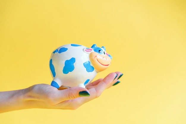 Skarbu banku w ludzkiej ręce na żółtym tle. ręka kobiety trzyma skarbonkę pełną pieniędzy.