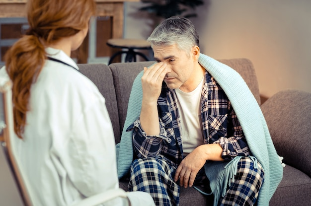 Skargi zdrowotne. przygnębiony posępny mężczyzna skarży się na swoje problemy zdrowotne podczas rozmowy ze swoim lekarzem