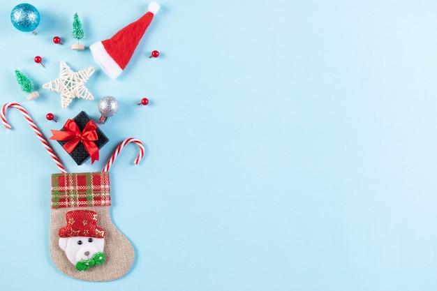 Skarpety i ozdoby świąteczne na pastelowym niebieskim tle. piękne kartki świąteczne z miejsca na kopię.